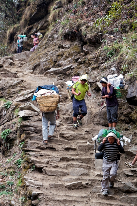 Local villagers go about their day carrying huge loads between villages.